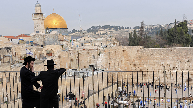 Ultra-Orthodox Jews stand on a balcony overlooking the Dome of the Rock and the Western Wall in the Old City of Jerusalem